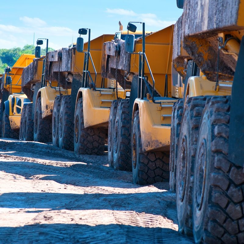 Dump trucks on a job site. Vesco offers lubrication services for heavy industrial equipment.